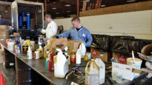 Spring drop-off volunteers place household toxic materials on the table to be sorted by chemists.