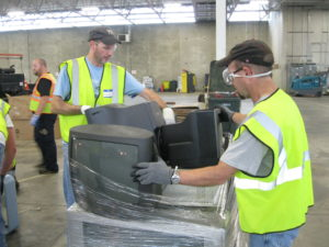Fall drop-off volunteers wrapping a pallet of electronics.
